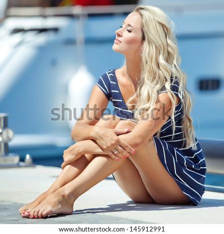 Beautiful sexy woman wearing sailor striped dress posing at the sea - stock photo
