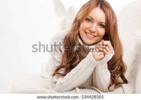 beautiful sexy woman wearing sweater sitting on the sofa and holding soft toy - stock photo