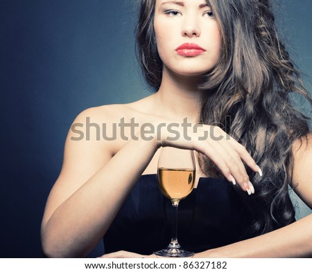 Beautiful sexy woman with a glass of white wine on a dark background. - stock photo