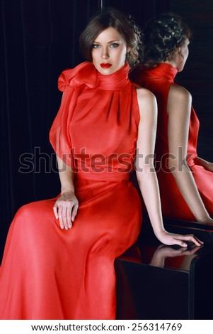 Beautiful sexy woman with beautiful makeup and red lipstick in red long evening dress of silk or chiffon with a large bow - stock photo