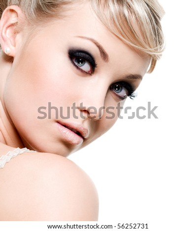 Beautiful sexy woman with black eye make-up. Close-up face isolated on white - stock photo