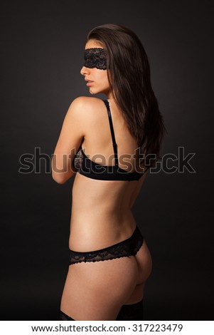 Beautiful sexy woman with black lingerie and lace blindfold. - stock photo