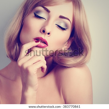 Beautiful sexy woman with bright eyes makeup touching her pink lips with desire. Toned closeup portrait - stock photo