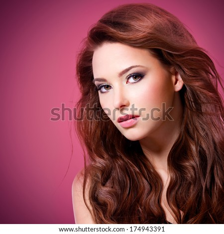 Beautiful sexy woman with brown long hairs looking at camera over pink background