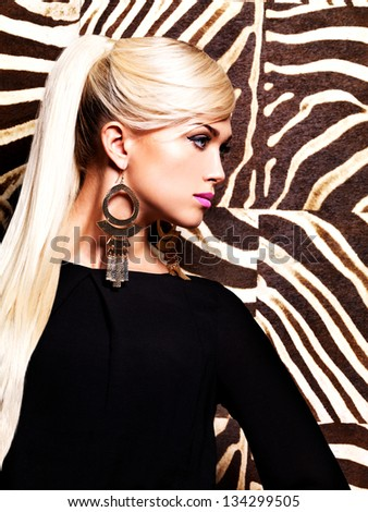 Beautiful sexy woman with fashion makeup on face and long white hairs. Profile Portrait  of glamour girl poses over creative striped background - stock photo