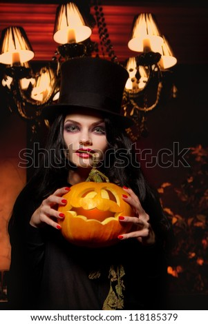 Beautiful sexy woman with halloween pumpkin over red background