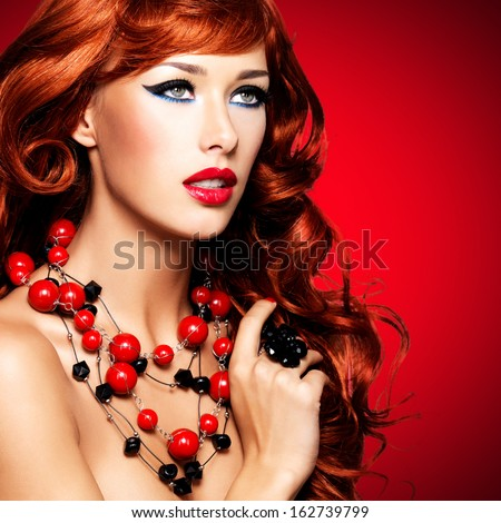 Beautiful sexy woman with long red hairs and bright red lips.  Closeup portrait  of  fashion model with curly hairstyle - at studio - stock photo