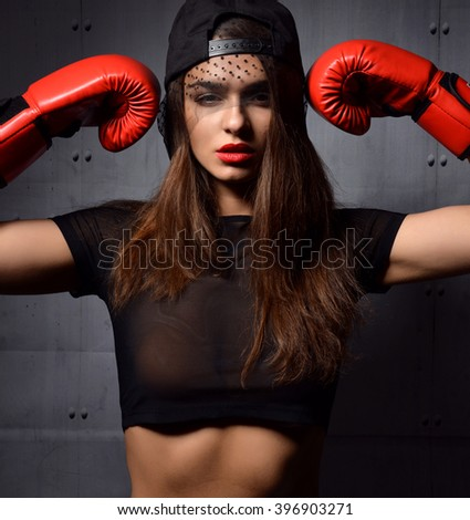 Beautiful sexy woman with red Boxing Gloves at the gym concept about sport fitness martial arts on a dark modern background - stock photo
