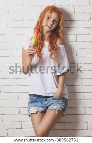 Beautiful sexy woman with red hair. Girl eat ice cream. - stock photo