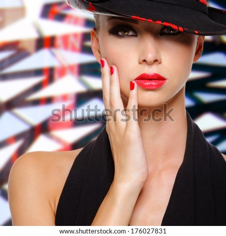 Beautiful sexy woman with red lips and nails in modern black hat - stock photo