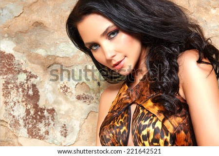 Beautiful sexy yang brunette woman with long black hair and evening makeup with gold accessesory in long dress wild animal print fashion style party - stock photo