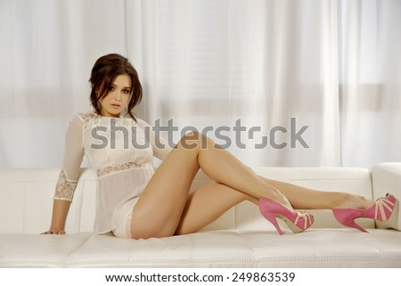 Beautiful sexy young adult attractive and sensuality pretty brunette woman on the white sofa in luxury style hotel apartment  - stock photo