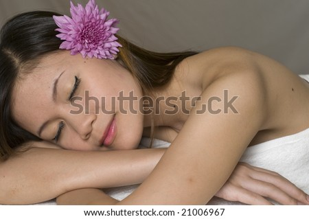 Beautiful sexy young Asian girl relaxing at a spa - stock photo