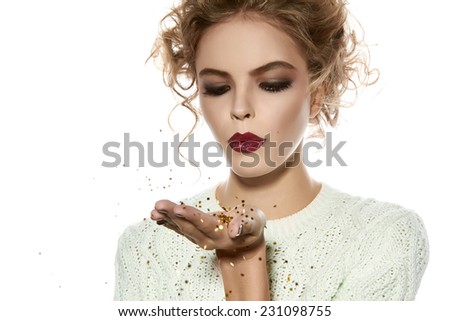 Beautiful sexy young blond girl with wavy hair bright evening make-up red lips long fluffy eyelashes holds palm with gold sequins in front of him and blows them a holiday New Year Christmas joy fun - stock photo