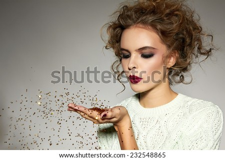 Beautiful sexy young blond girl with wavy hair bright evening make-up red lips long fluffy eyelashes holds palm with gold sequins in front of her and blows them a holiday New Year Christmas joy fun - stock photo