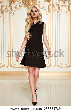 Beautiful sexy young blonde girl with long thick wavy hair thin slender figure perfect body and pretty face make-up wearing a little black dress high heels - stock photo