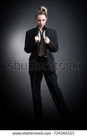 Beautiful sexy young blonde woman in a dark business suit, white shirt and tie posing on a gray background