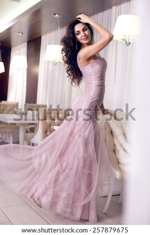 Beautiful sexy young brunette woman with long wavy hair thin slender figure perfect body and pretty face make-up wearing a purple evening skinny dress and jewelry  - stock photo