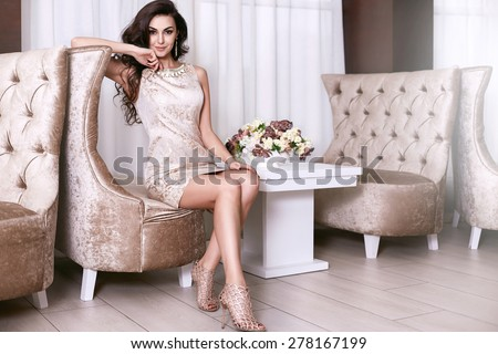 Beautiful sexy young brunette woman with long wavy hair thin slender figure perfect body and pretty face make-up wearing a beige evening skinny dress and jewelry   - stock photo