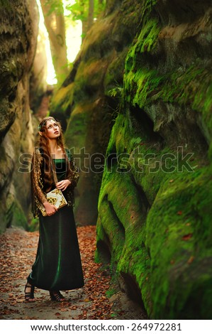 Beautiful sexy Young Female elf in the mountains with a book - stock photo