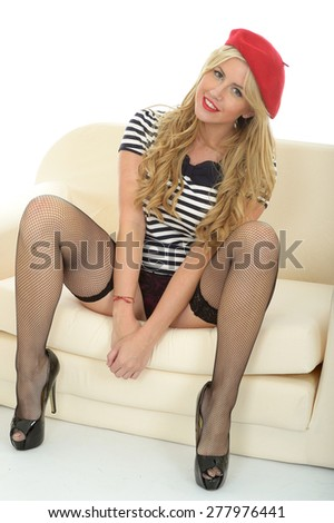 Beautiful Sexy Young French Woman Sitting On A Sofa In A Red Beret Black Stockings and a Striped Shirt - stock photo