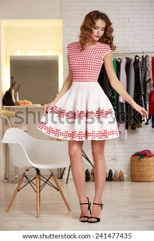Beautiful sexy young girl with blond curly hair and bright evening make-up wearing a short cocktail dress pink photographed in the interior of  clothing store thin body shape diet elegant at the party - stock photo