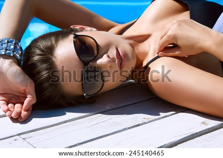 Beautiful sexy young girl with perfect slim figure with long wet hair and bathing suit in fashionable stylish sun glasses sitting on the steps of swimming pool swim, sunbathe, have fun at beach party - stock photo