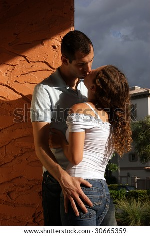 beautiful sexy young lovers kissing in the hot afternoon sun up against a wall in romantic tropical setting with heavy shadows and vibrant colors - stock photo