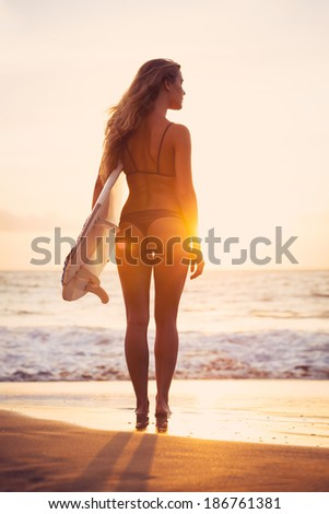 Beautiful sexy young surfer girl in bikini with surfboard on the beach at sunset - stock photo