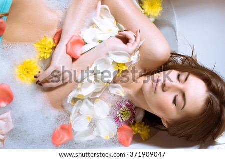 Beautiful sexy young woman having bath with flower petals