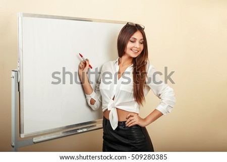 Beautiful sexy young woman holding a marker and writes on the whiteboard