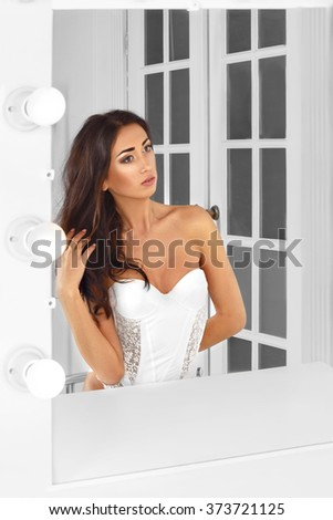 Beautiful sexy young woman in  lingerie  looking into a mirror at herself.  Woman  with curly hair  - stock photo