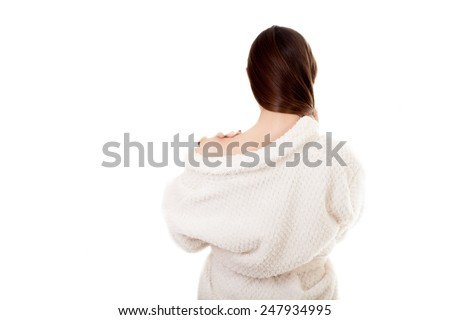 Beautiful sexy young woman in white bathrobe undress exposing one shoulder, isolated, white background. Cozy, beauty, comfort, wellbeing, healthcare, bodycare concepts. Back view. - stock photo