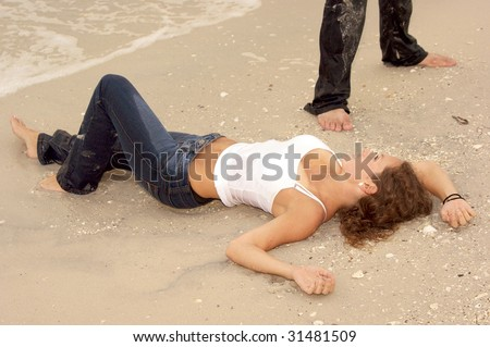Beautiful sexy young woman laying on the beach in wet jeans looking up at man who is standing above her out of frame - stock photo