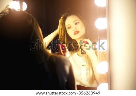 Beautiful sexy young woman looking into a mirror at herself and use perfume on her neck. - stock photo