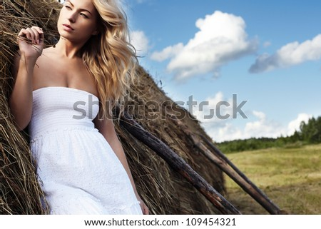 Beautiful sexy young woman near a haystack - stock photo