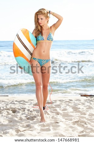 Beautiful sexy young woman surfer girl in bikini with surfboard at a beach  - stock photo