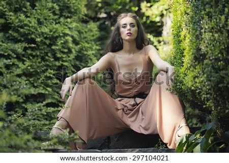 Beautiful sexy young woman with bright makeup and long curly brunette hair in summer overalls with deep decollete sitting in green garden with lush plants sunny day outdoor, horizontal picture - stock photo