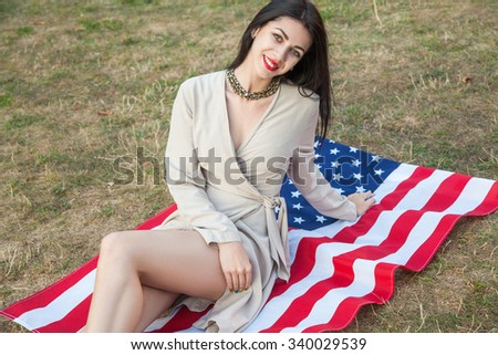 Beautiful sexy young woman with classic dress lying down on american flag in the park. fashion model holding us smiling and looking at camera. business style clothing USA lifestyle with toothy smile.
