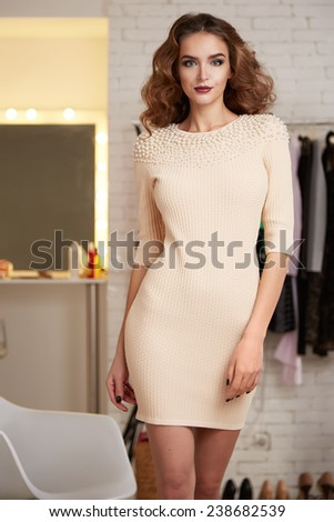 Beautiful sexy young woman with curly brown hair bright evening make-up wearing a short cocktail dress cream colored pearls perfect body shape sports a healthy diet, chic luxury of  interior at party - stock photo