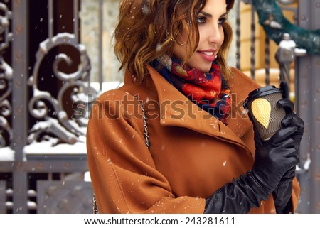 Beautiful sexy young woman with curly brown hair with bright makeup wearing brown coat goes on snow-covered street past shops with a cup of hot coffee, cappuccino, tea, Christmas and New Year Winter - stock photo