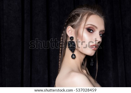 beautiful sexy young woman with dark hair braided with bright makeup and fashion bizhuterieyker earrings and ring, fashion jewelry shooting on a black background in the studio, hard light