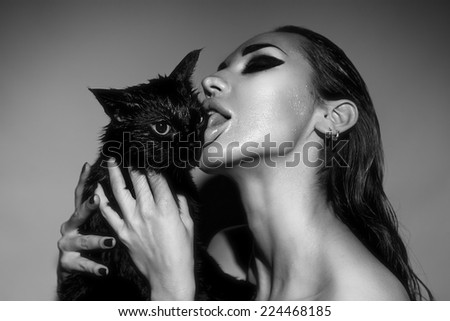 Beautiful Sexy Young Woman with Glamour make-up licking a black cat. Fashion Beauty studio shot. Beautiful sensitive Girl Face, black and white - stock photo