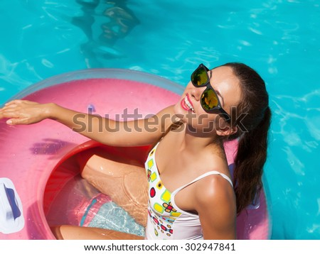 Beautiful sexy young woman with perfect slim figure with long dark hair and wet bathing suit fashion in stylish glasses from the sun is sunning by swimming pool swim, sunbathe have fun at pool party