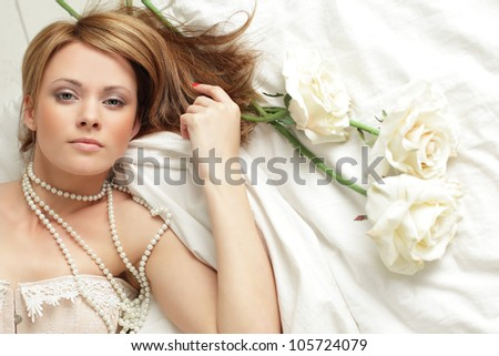 Beautiful sexy young woman with rose lying on the bed