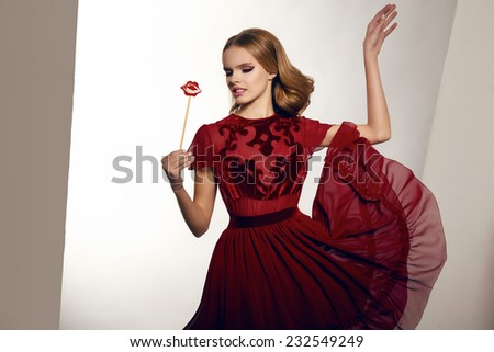 Beautiful sexy young woman with wavy blond hair and soft natural make-up in evening gown of chiffon and silk embroidered, holding a candy on a stick in the form of candy lips - stock photo