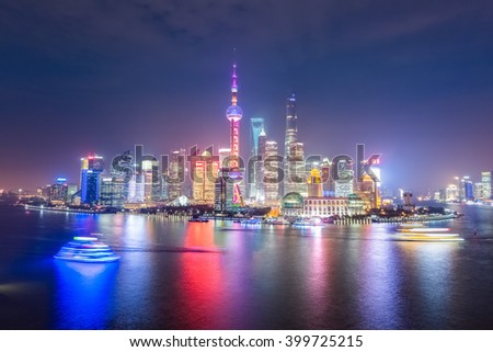 beautiful shanghai skyline at night , light trails from cruise ship in huangpu river, China.