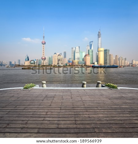 beautiful shanghai skyline in afternoon with wooden floor  - stock photo