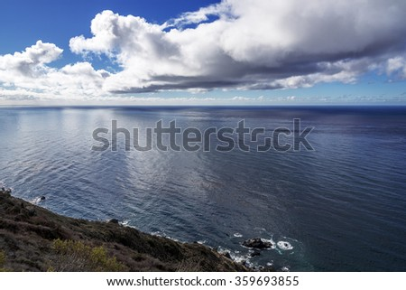 Beautiful shimmering  blue sea, ocean,  and white puffy clouds, along steep sheer jagged cliffs, near Carmel, CA. traveling the Big Sur Highway (Highway 1), on the California Central Coast. - stock photo