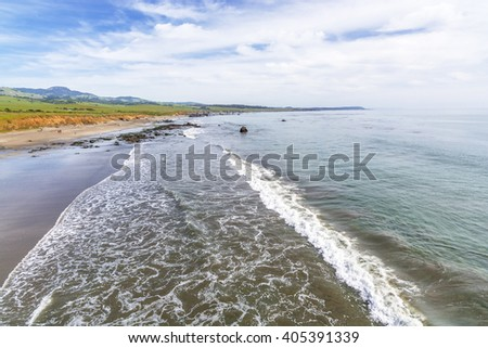 Beautiful shimmering blue sea, white clouds & waves, gently crashing on San Simeon Beach, while people are enjoying a walk on the beach & beautiful green hills in the background, near San Simeon, CA.